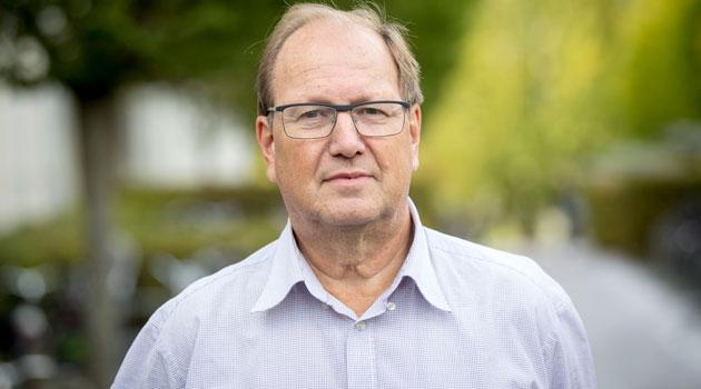 Porträttbild av Leif Andersson med grönska i bakgrunden.