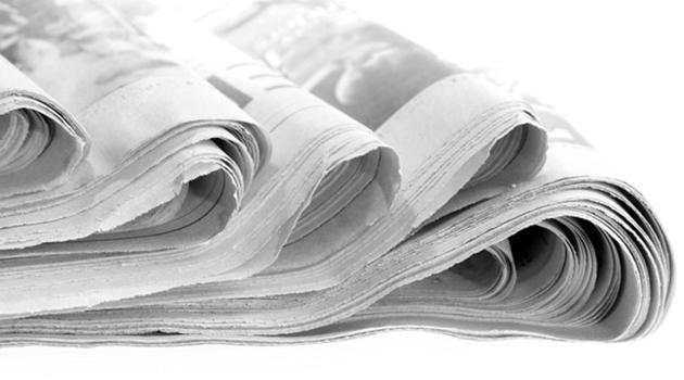 Närbild på vikta dagstidningar.