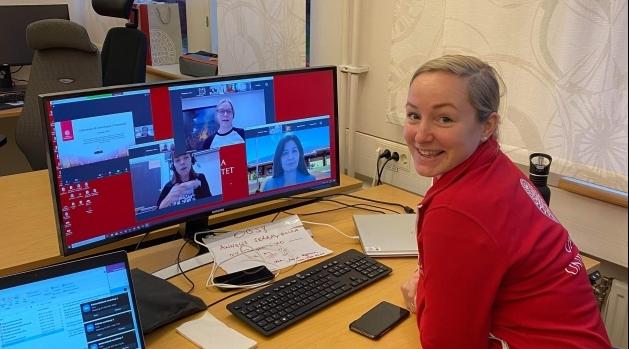 Kvinna framför skärm med mötesdeltagare.