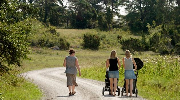 Mammor med barnvagnar som är ute på promenad.