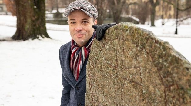 Marco Bianco is standing by a runestone in the University park.