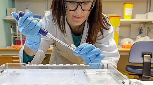 Maria Karlgren med en pipett i labbet
