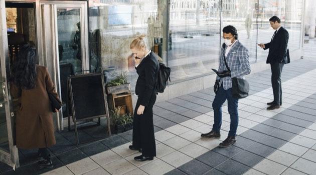 Några personer står och köar med social distans och en av dem har munskydd.