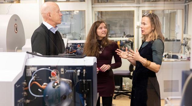 Tre personer står vid en mass-spektrometer.