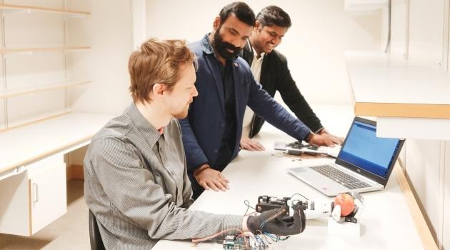 Män i labb med konstgjord arm