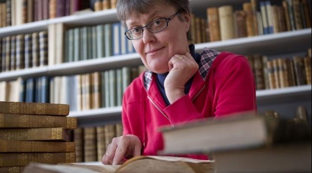 Maria Ågren sitter med fingret i en uppslagen bok.