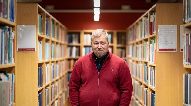 Olle Lundin fotograferad bland bokhyllor.