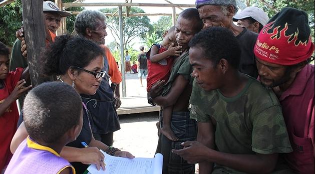 Sittande kvinna med pappersformulär samtalar med personer som står runt omkring.