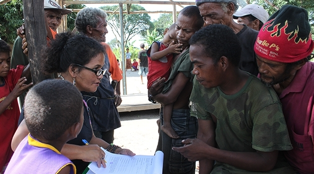 A woman with paper and a pen is talking to a group of people.