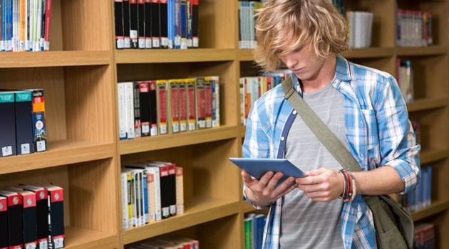 Pojke står med läsplatta i ett bibliotek