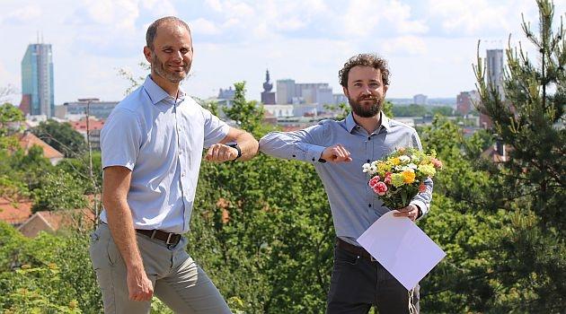 Två män framför grönområde med hus i bakgrunden