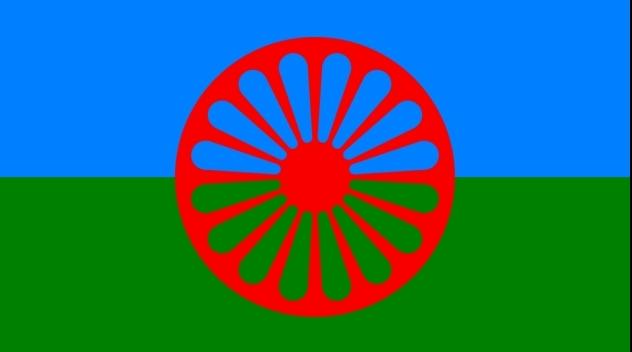 Romska flaggan. Blått fält överst, grönt underst, i mitten rött hjul.