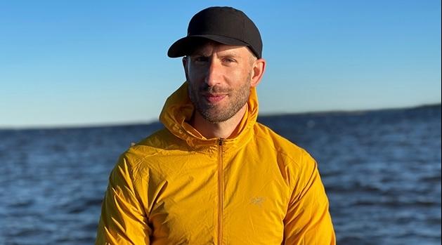 Alexander Rozental står vid havet och är iförd svart keps och gul jacka.