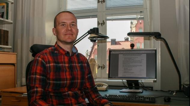 Fotografi på Sami Uljas på hans tjänsterum.