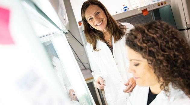 En leende Sandra Kleinau i labbet med en kollega i förgrunden.