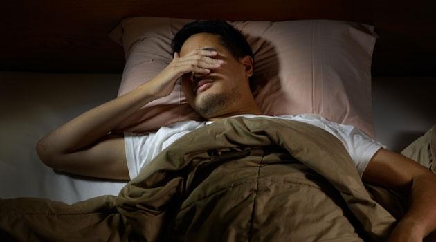 Man ligger i sängen och håller handen för sina ögon.
