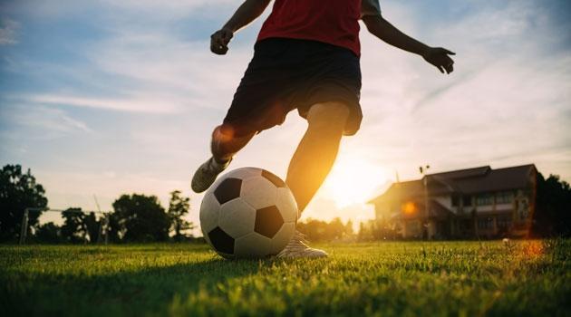 Kille som spelar fotboll på gräsplan.