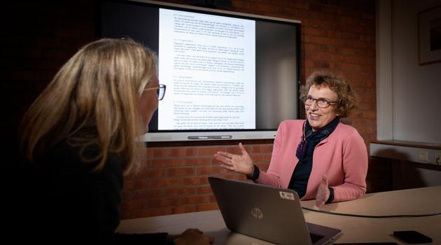 Kristina Asker sitter och pratar med en person vid en bildskärm med text