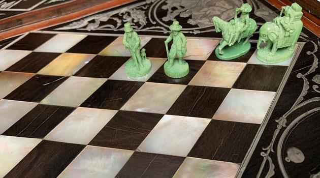 Skulpterade schackpjäser på ett bräde av ebenholts, pärlemor och inlagt silver