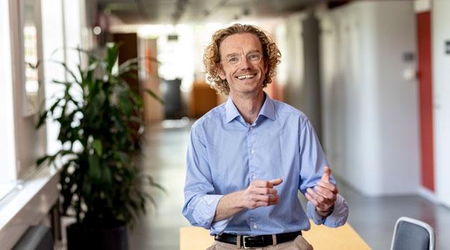 Thomas Schön ser glad ut och gestikulerar i en korridor.