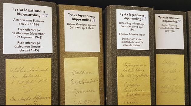 foto på fyra pärmryggar ur arkivet med beskrivning av deras innehåll
